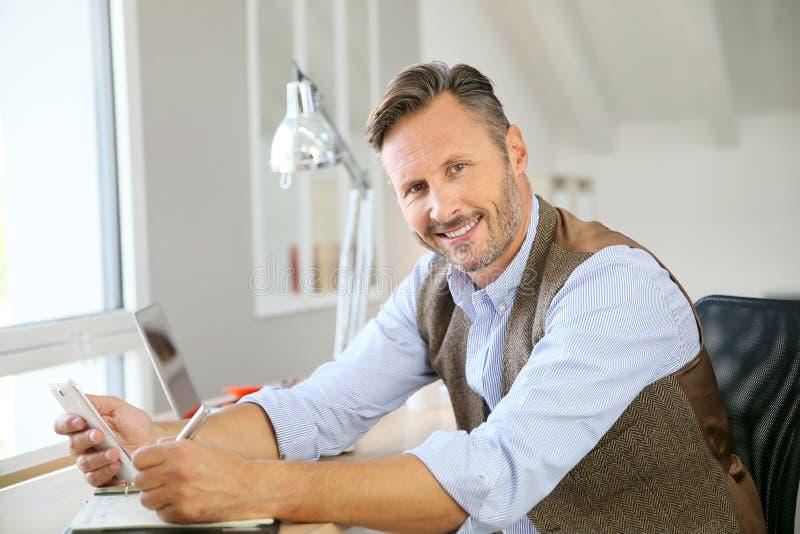 在家坐办公室的英俊的人使用智能手机 免版税库存照片