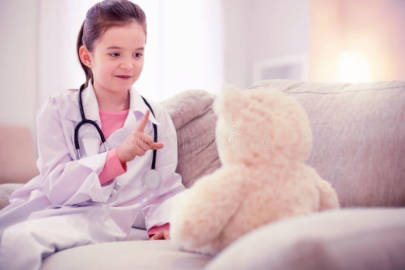 在家坐单独使用与她的玩具熊的逗人喜爱的女孩 库存照片