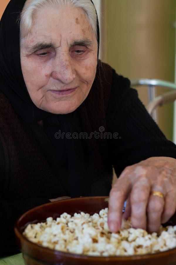在家坐和吃玉米花的祖母 库存图片