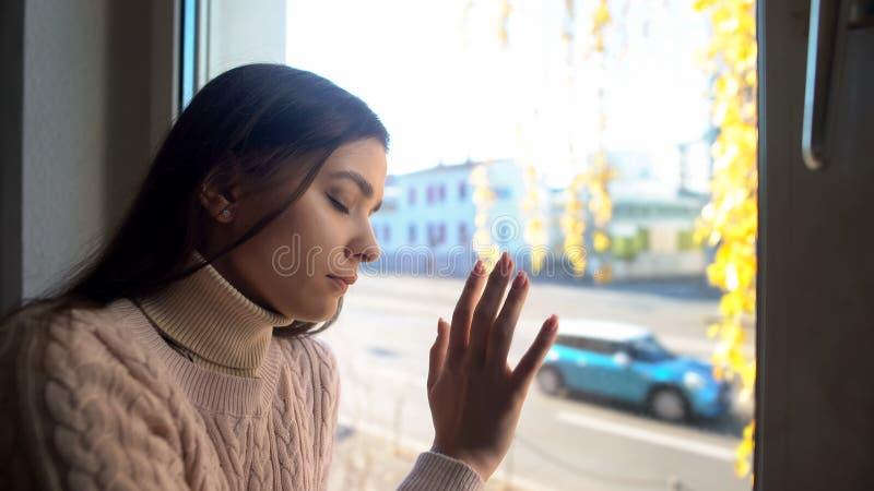 在家坐和接触窗口,秋天忧郁,哀痛的沉思女孩 免版税图库摄影
