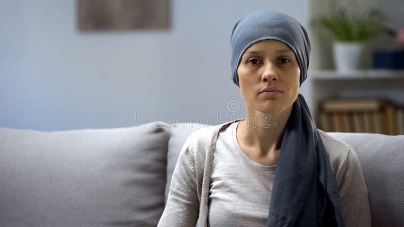 在家坐和调查照相机,背景的化疗以后的妇女 免版税库存图片