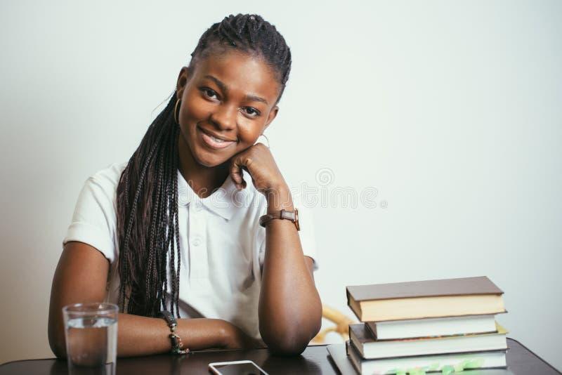 在家坐在与书的桌上的非洲少妇 免版税库存照片
