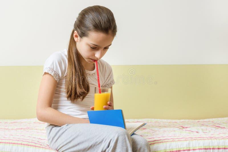 在家坐在与杯的床上的儿童女孩新鲜的橙汁过去和看书 库存照片