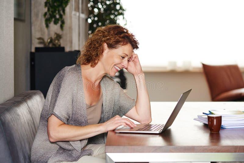 在家坐在与膝上型计算机微笑的桌上的妇女 免版税库存图片