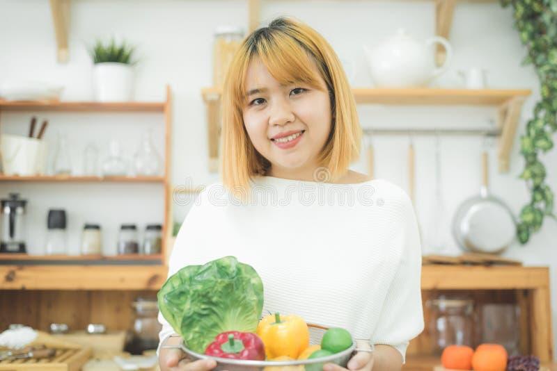 在家坐在厨房和拿着里的微笑的亚裔美丽的妇女色拉盘 库存图片