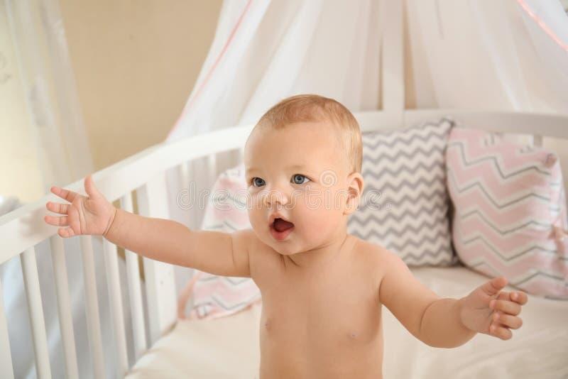 在家坐在小儿床的逗人喜爱的矮小的婴孩 库存图片