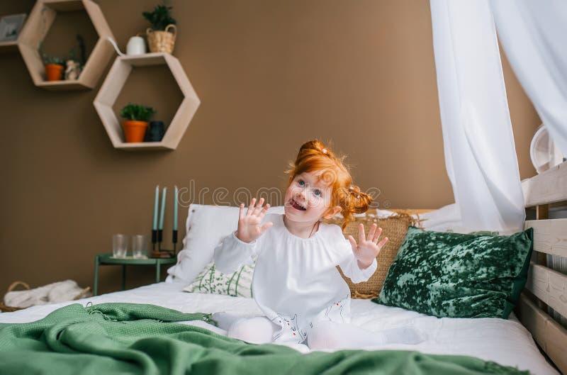 在家坐在床上的滑稽的红头发人孩子 他有在他的面孔的一副滑稽的鬼脸 库存图片