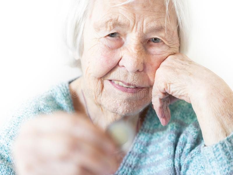 在家坐在桌上和看凄惨地从退休金的仅剩余的硬币的哀伤的年长妇女在她的手上 库存图片