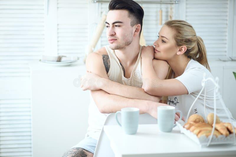 在家坐在桌上在厨房里和看窗口的年轻美好的爱恋的夫妇,当食用早餐时 免版税库存照片