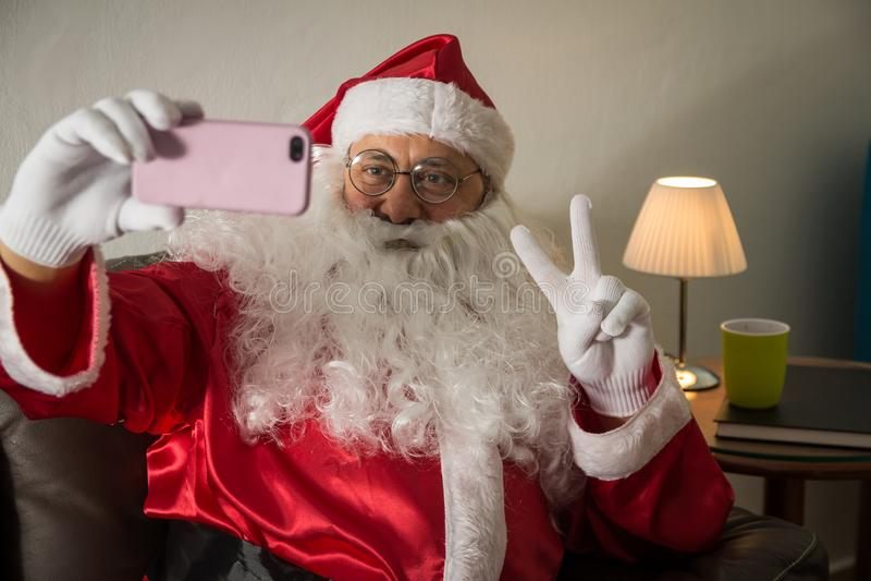 在家坐在沙发的圣诞老人项目正面图使用细胞pho 免版税库存照片