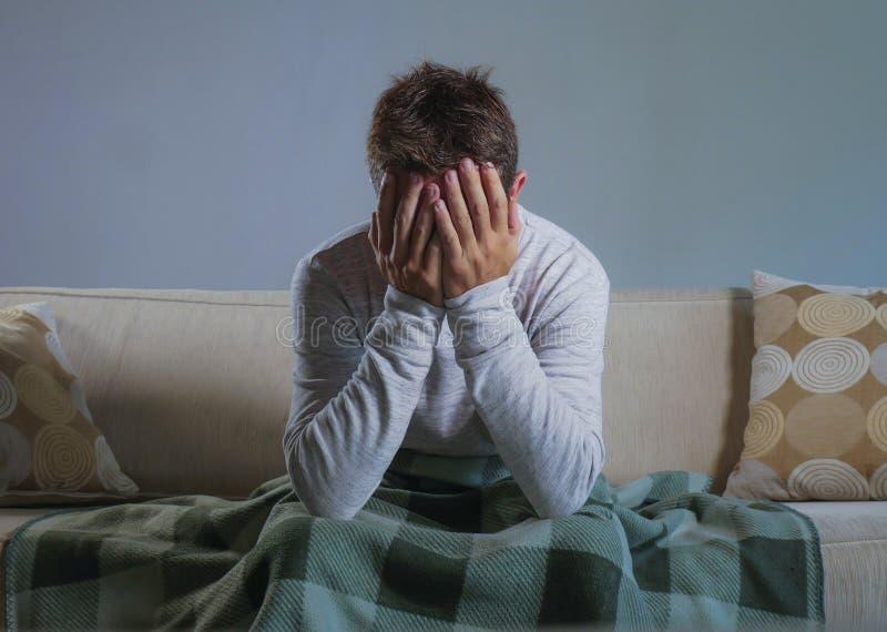 在家坐在沙发长沙发覆盖物面孔的年轻哀伤和绝望人用遭受消沉和重音的手单独哭泣 免版税图库摄影