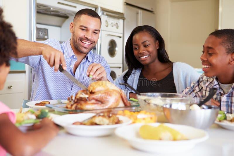 在家坐在表附近的家庭吃膳食 免版税库存照片