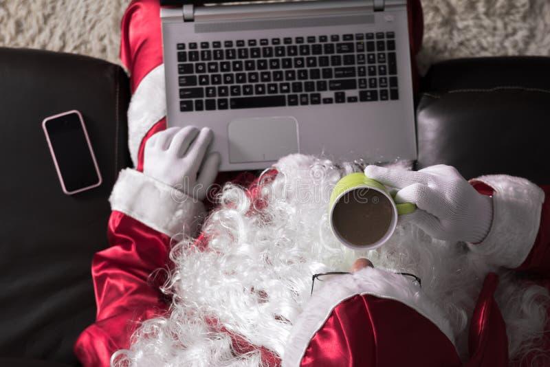 在家坐在长沙发的圣诞老人项目顶视图使用通信和休闲的膝上型计算机 喝拿铁 免版税图库摄影