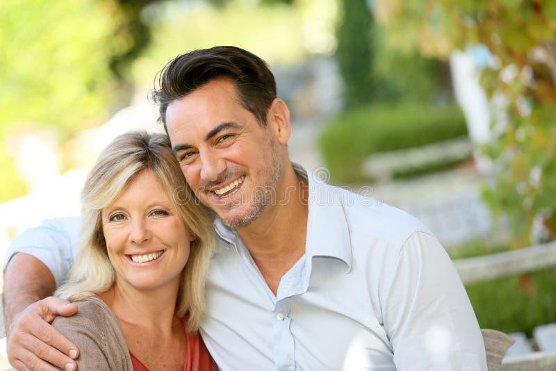 在家坐庭院的爱恋的成熟夫妇 免版税库存图片