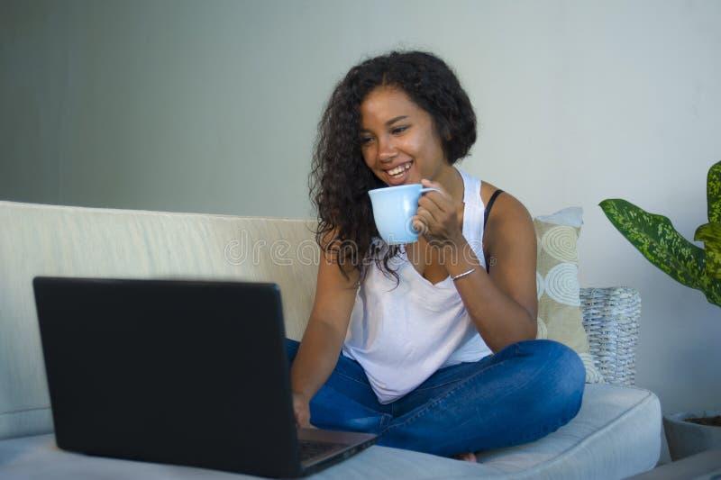 在家坐沙发与便携式计算机饮料的年轻可爱和轻松的黑人非裔美国人的学生妇女长沙发网络 免版税库存图片