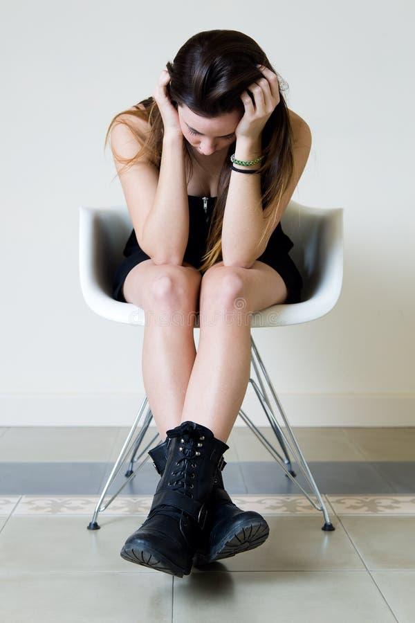 在家坐沮丧的少妇 免版税库存图片