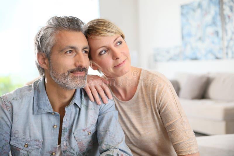 在家坐爱恋的成熟的夫妇 库存图片