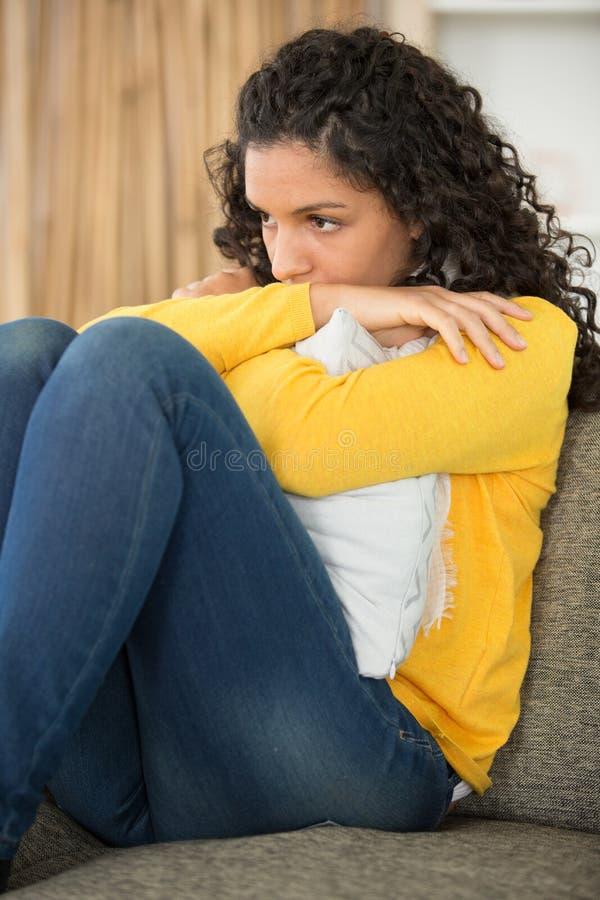 在家坐由沙发的哀伤的年轻女人 库存照片
