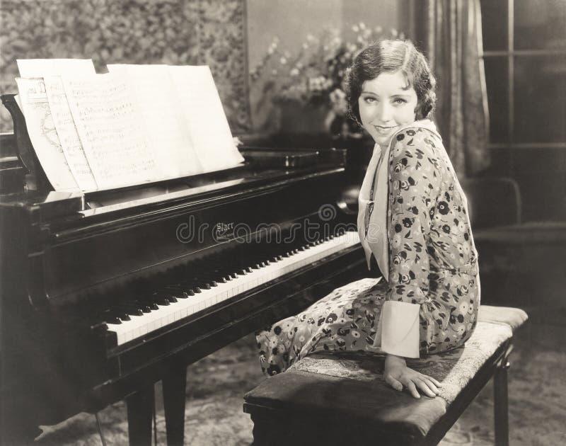 在家坐由钢琴的微笑的妇女 免版税库存照片