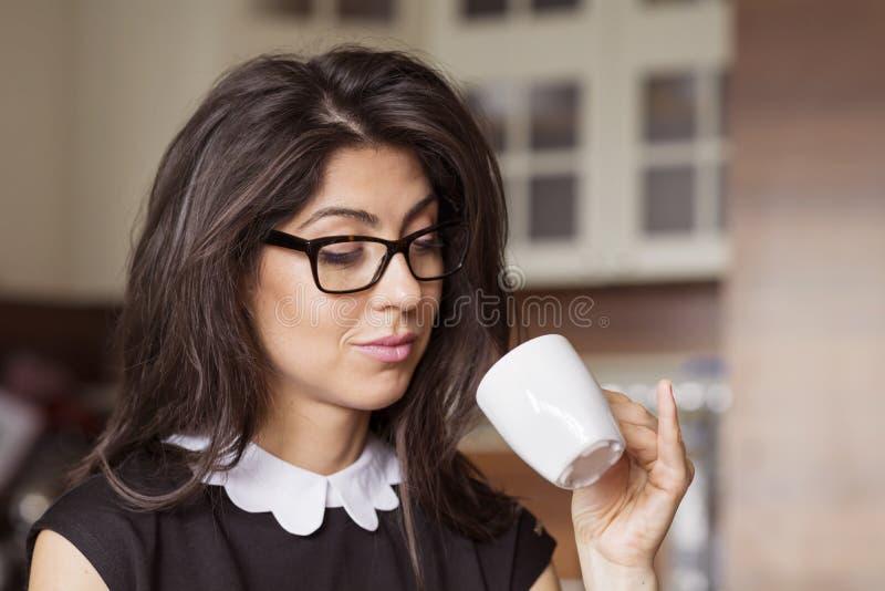 在家坐美丽的少妇,饮用的咖啡 库存图片