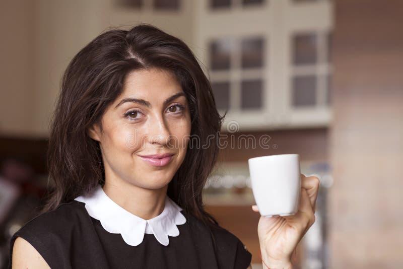 在家坐美丽的少妇,饮用的咖啡 图库摄影