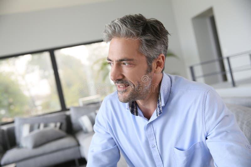 在家坐英俊的成熟的人 免版税库存照片