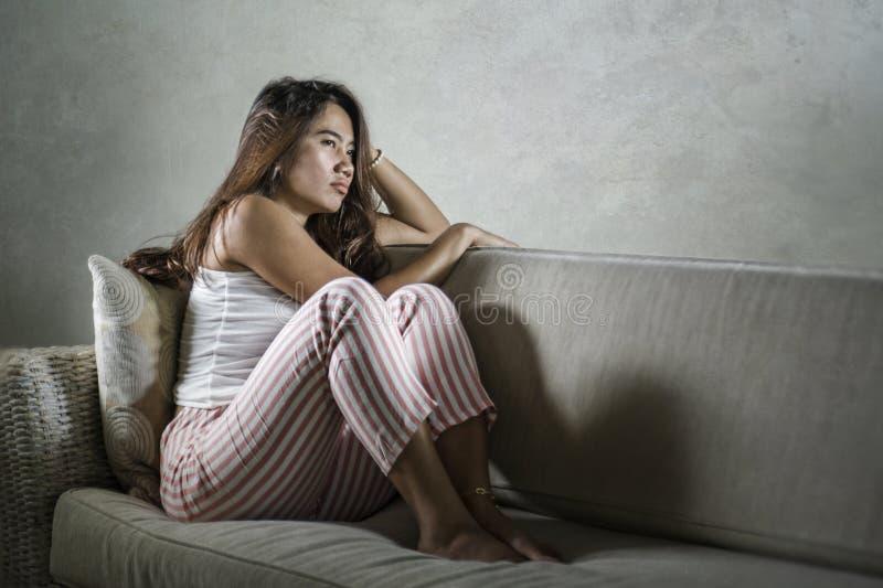 在家坐长沙发的年轻哀伤和沮丧的亚裔印度尼西亚妇女哭泣沮丧和生气痛苦重音和消沉 库存照片