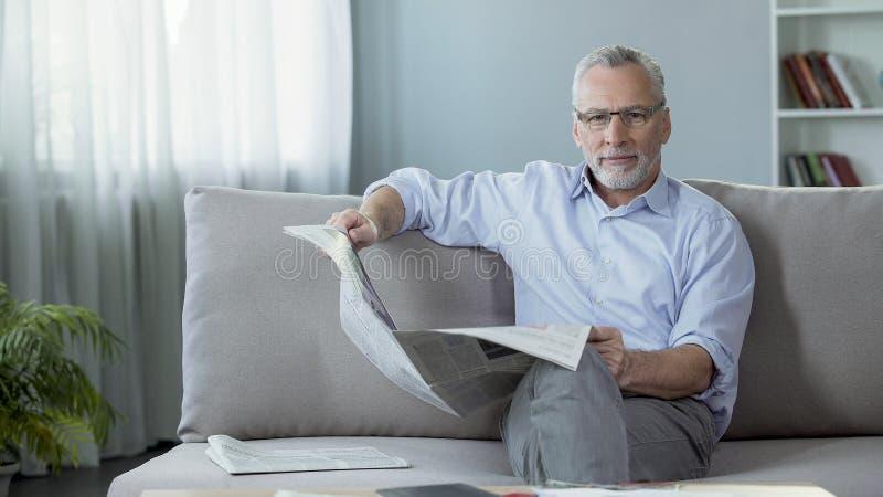 在家坐长沙发,拿着报纸和调查照相机的老人 免版税图库摄影