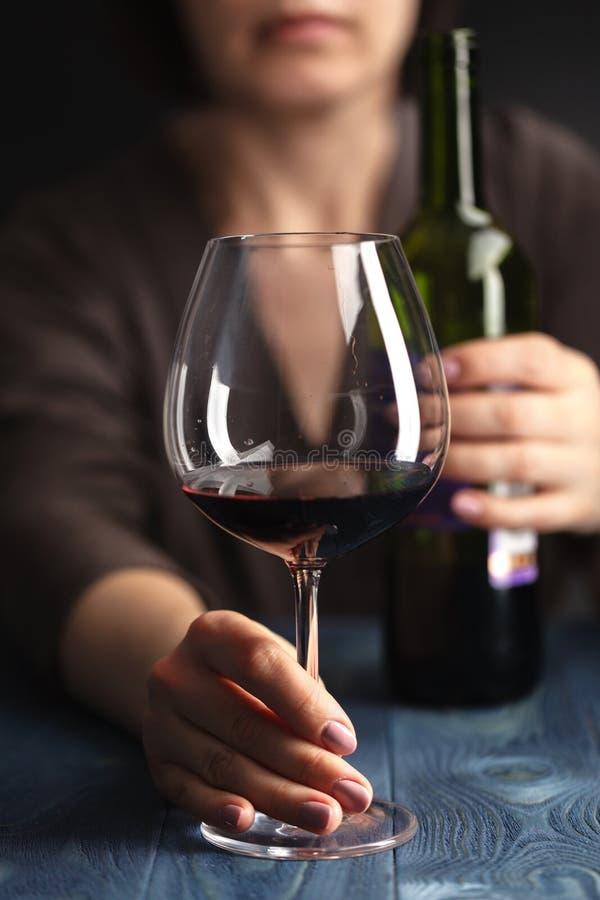 在家坐饮用的红葡萄酒的哀伤和被浪费的醺酒的妇女 免版税库存图片