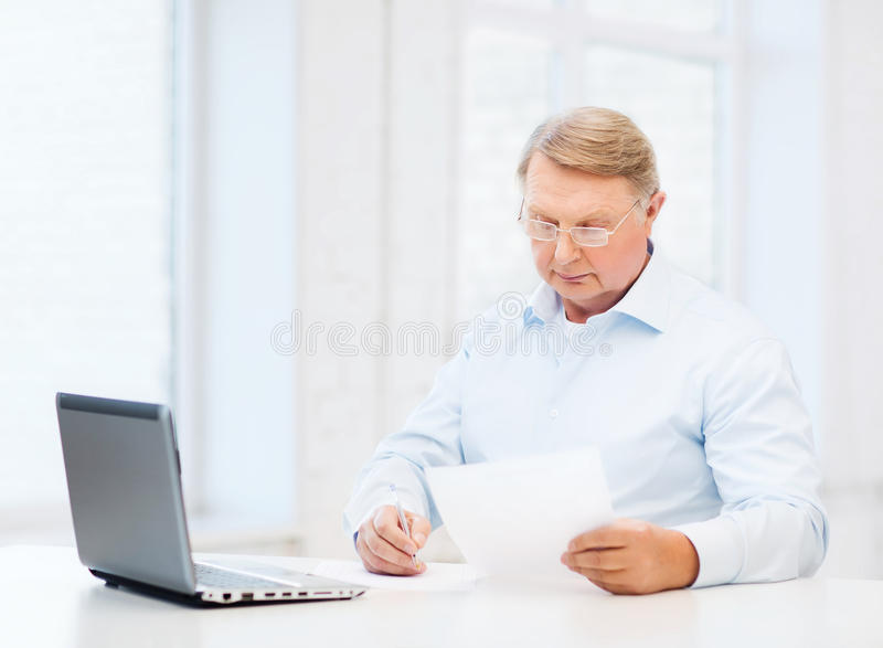 在家填装形式的镜片的老人 免版税库存照片