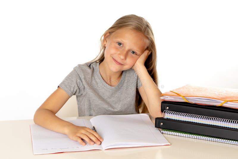 在家学习在有一本学习参考书的一张书桌上的逗人喜爱的女孩在白色背景 库存图片