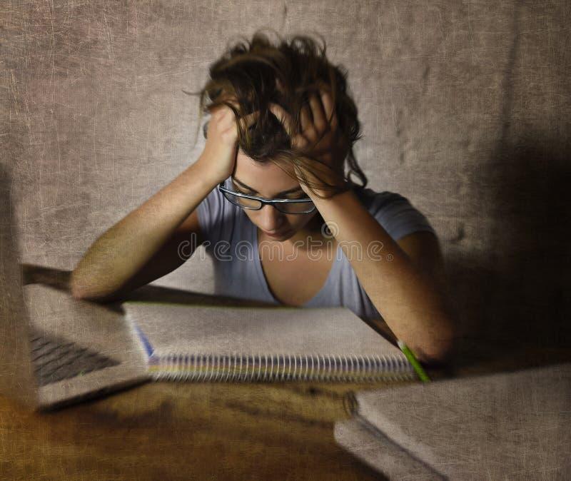在家学习夜间疲倦的便携式计算机的年轻学生女孩准备被用尽的检查 库存照片