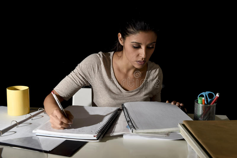 在家学习夜间看起来的准备的检查的年轻繁忙的美丽的西班牙女孩被集中 免版税库存照片