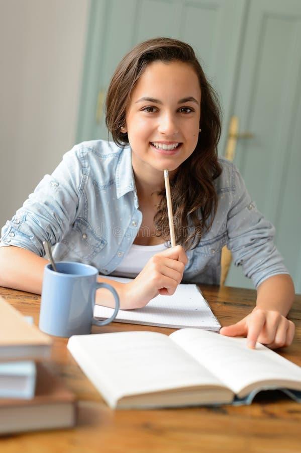 在家学习微笑的学生十几岁的女孩 免版税图库摄影