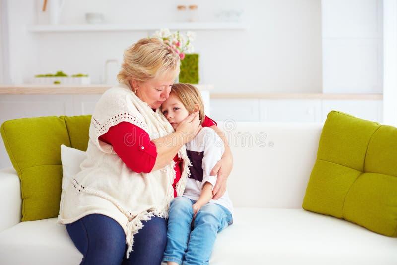 在家安慰她哀伤的孙子的老婆婆 免版税图库摄影
