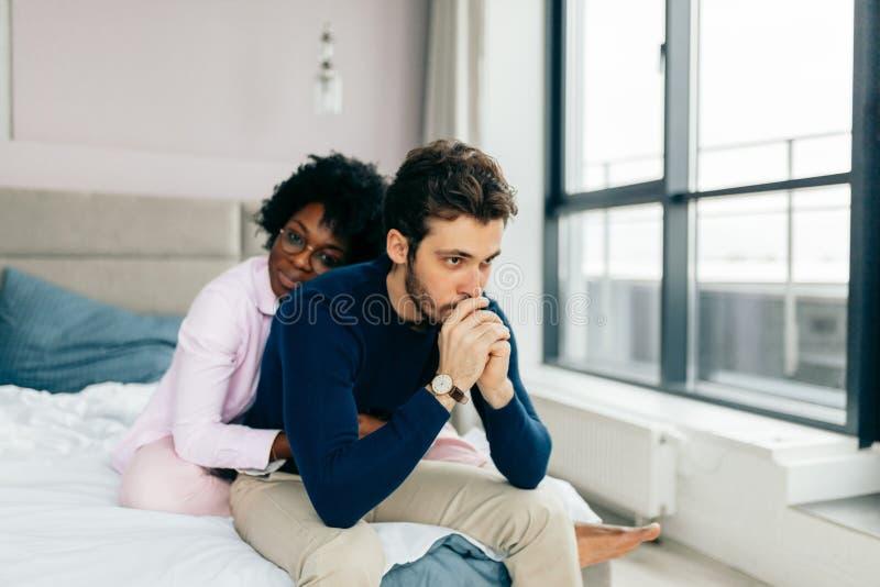 在家安慰她的沙发的可爱的非洲女孩生气男朋友 库存照片