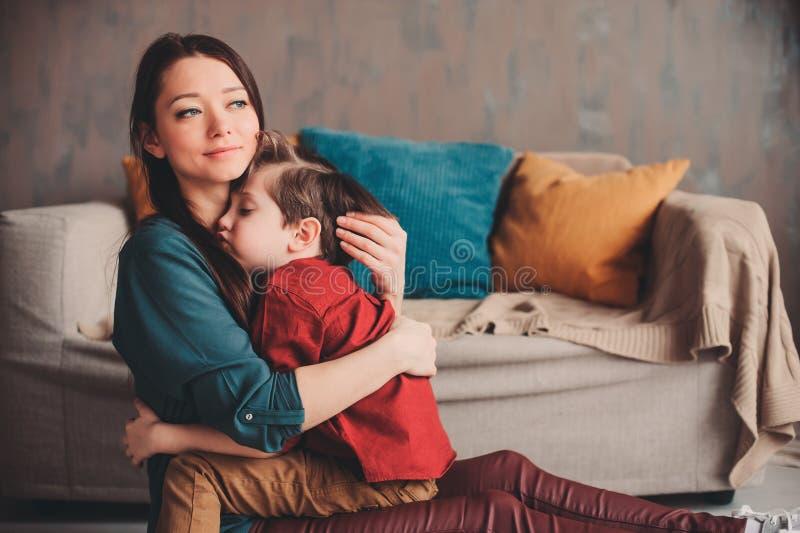 在家安慰小孩儿子的愉快的爱恋的母亲室内画象  库存照片