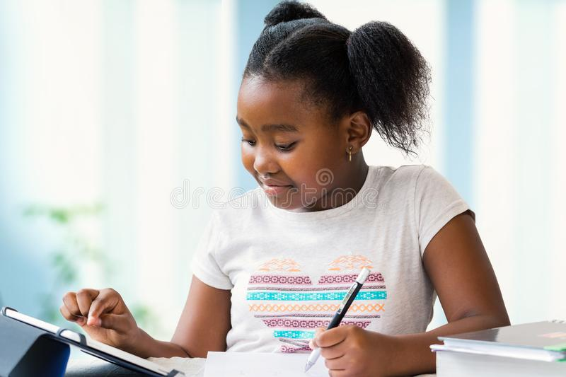 在家完成学校工作在数字式片剂的逗人喜爱的非洲女孩 免版税库存图片