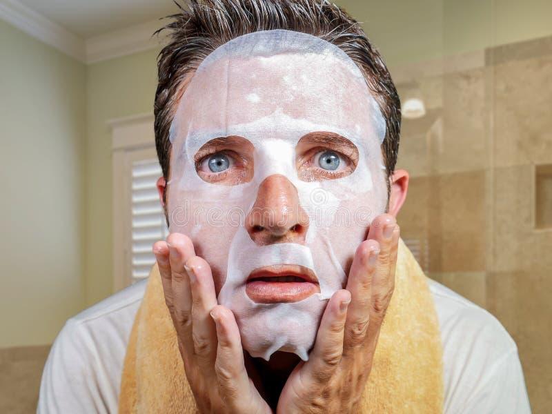 在家尝试使用秀丽纸面膜的年轻奇怪和滑稽的人洗涤学会在惊奇的面孔的防皱治疗 免版税库存图片