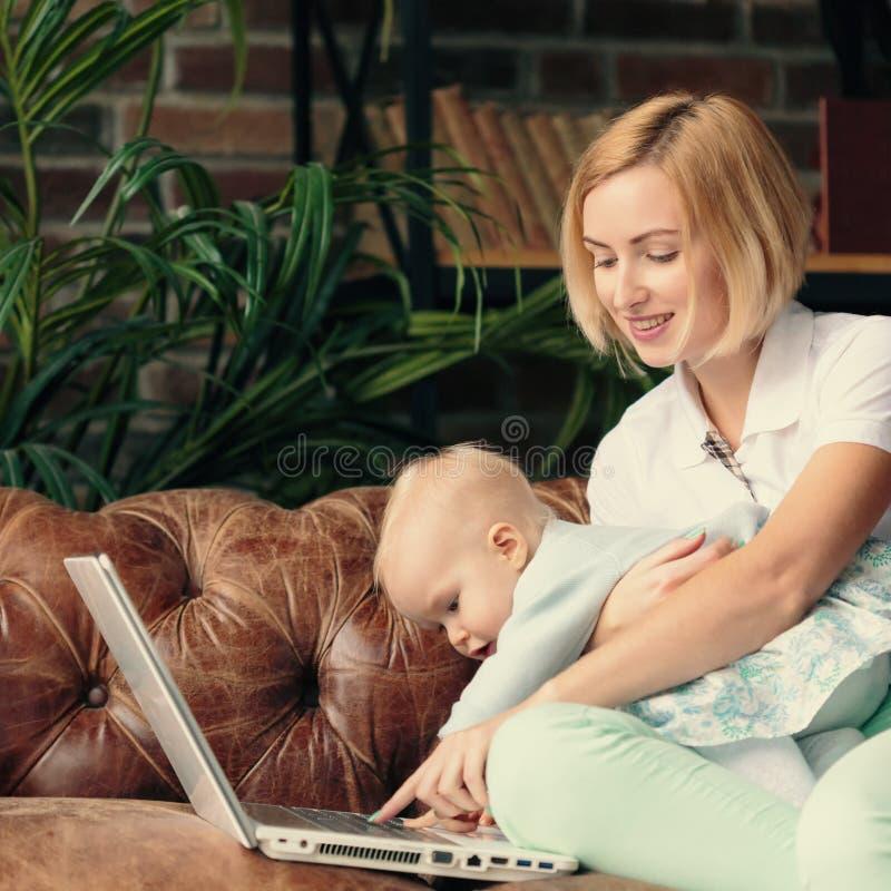 在家工作与女婴的年轻母亲 图库摄影