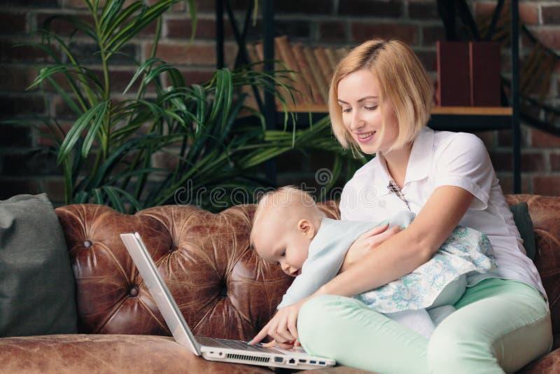 在家工作与女婴的年轻母亲 库存照片