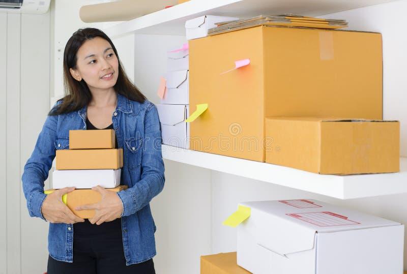 在家工作办公室检查命令的亚裔女商人准备好对邮寄或运输与箱子和稠粘的便条纸 免版税库存图片