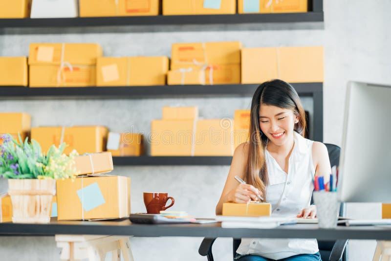 在家工作办公室的年轻亚洲小企业主,注意关于购买订单的 网上营销包装的交付 免版税库存图片