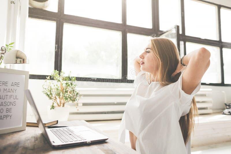 在家工作在膝上型计算机后和伸她的手的年轻女商人 创造性的斯堪的纳维亚样式工作区 免版税库存图片