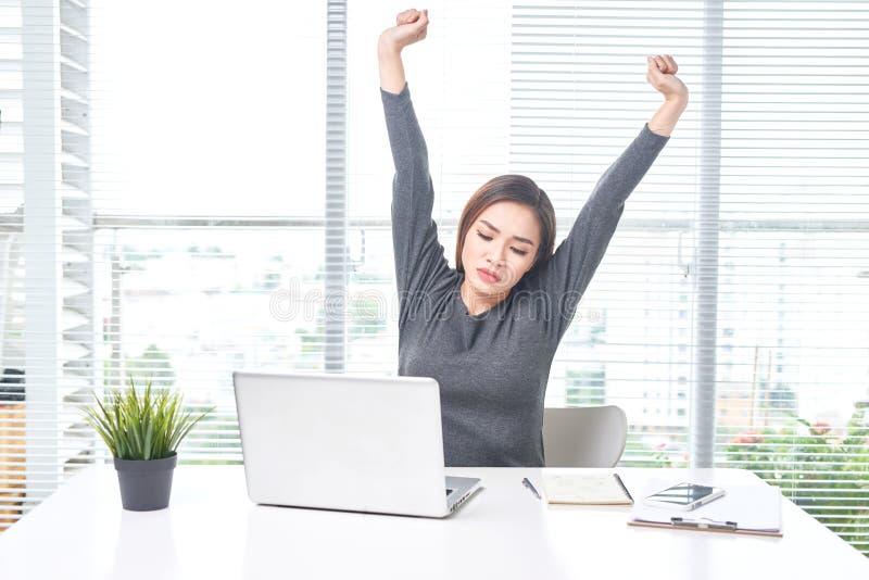 在家工作在膝上型计算机后和伸她的手的年轻女商人 免版税库存照片