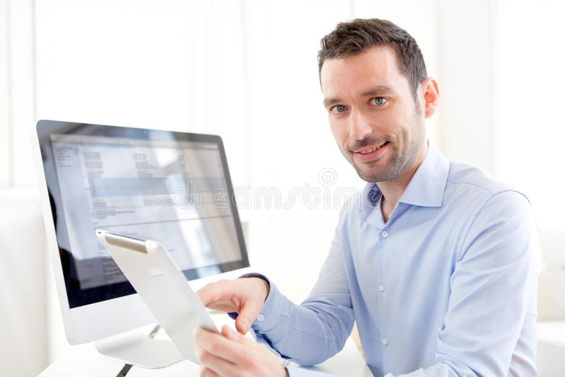 在家工作在他的片剂的年轻商人 库存图片