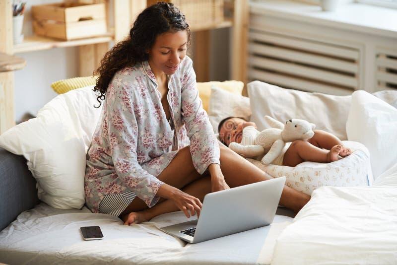 在家工作多任务非洲的母亲 免版税库存图片