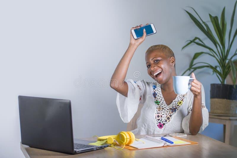 在家工作有便携式计算机的年轻愉快和可爱的黑人美国黑人的行家妇女办公室使用机动性的互联网 库存照片