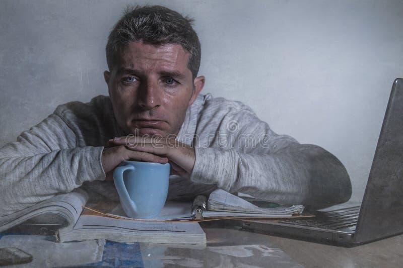 在家工作有便携式计算机的年轻担心和沮丧的人夜间书桌感觉被挫败的和疲倦的认为的论文 免版税库存照片