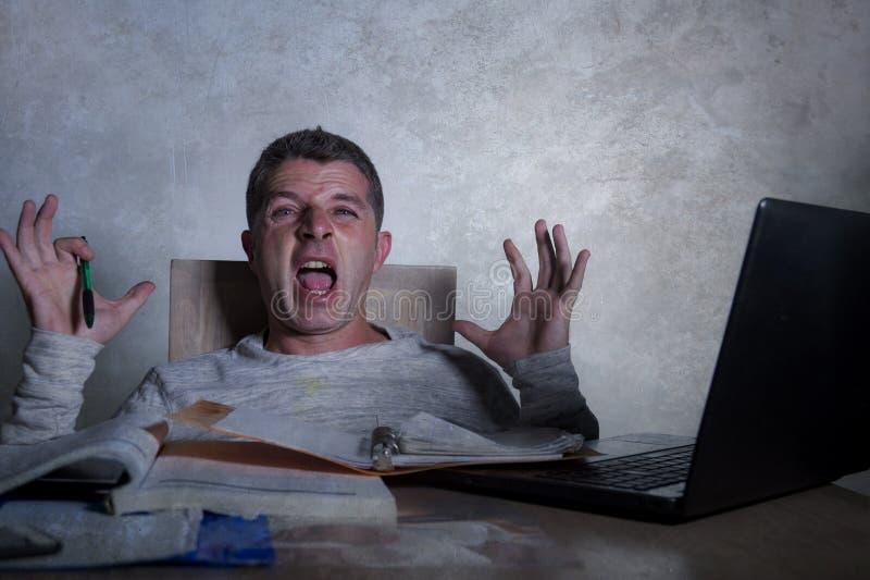 在家工作有便携式计算机的年轻担心和绝望人夜间书桌尖叫的被挫败的和疲倦的认为的pap 库存照片